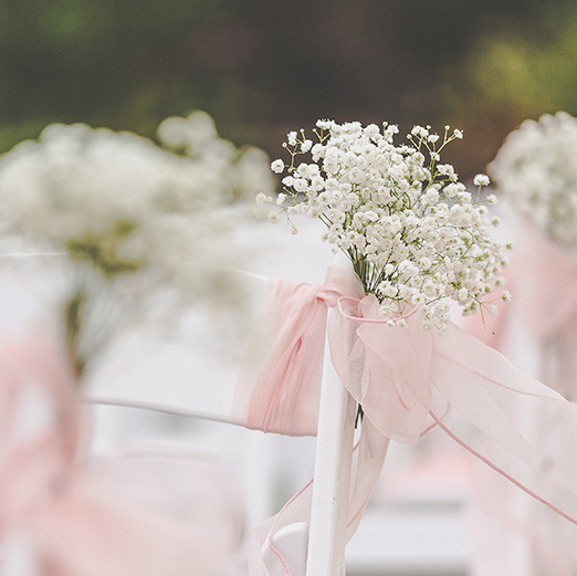 The couple decorated the chairs for their wedding ceremony with baby's breath wedding flowers