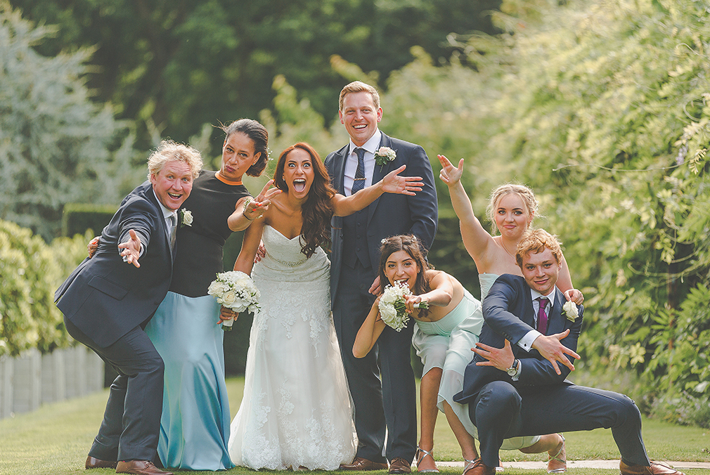The happy couple strike a fun pose with their wedding party at this beautiful Essex wedding venue