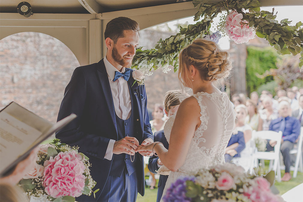 Bride and groom exchanging rings during an outdoor ceremony at Braxted Park