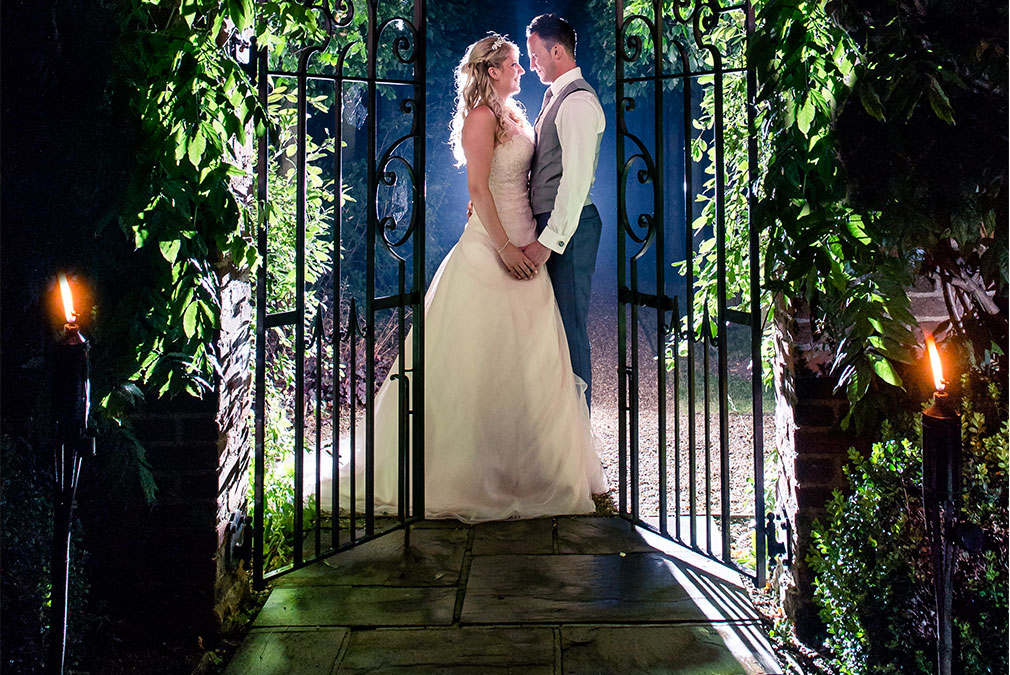 Bride and groom posing for photos in the gardens of Braxted Park in Essex