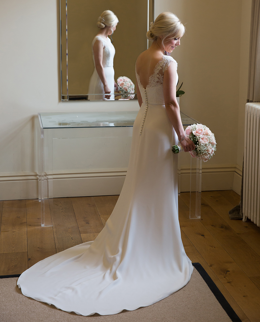 The bride stands in her wedding dress holding a bouquet of wedding flowers – wedding venues Essex