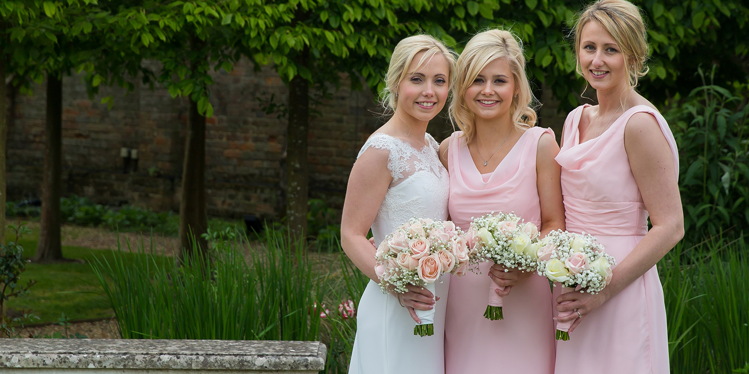 The bride stands with her two bridesmaids who each wear blush pink bridesmaid dresses