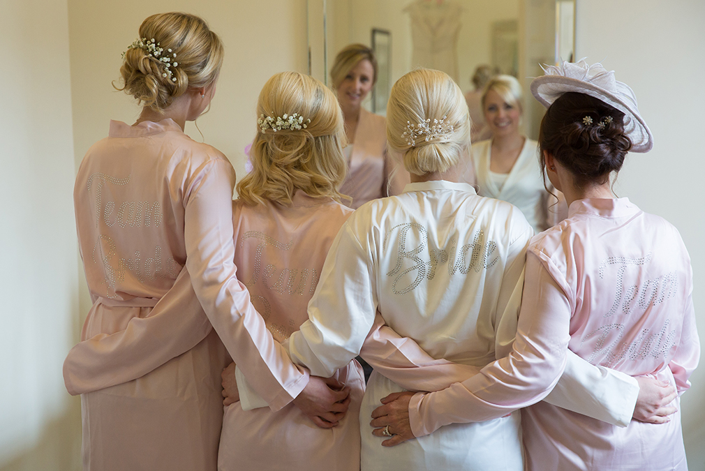 The bride enjoys her wedding preparations with her bridesmaids and mother each wearing robes