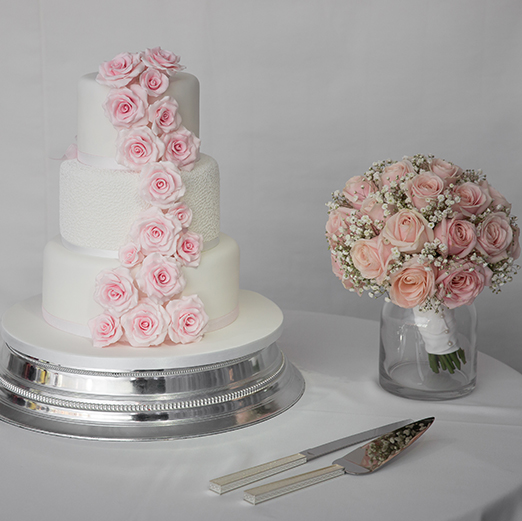 The couple chose a three-tier white wedding cake decorated with pink fondant flowers – wedding cake designs