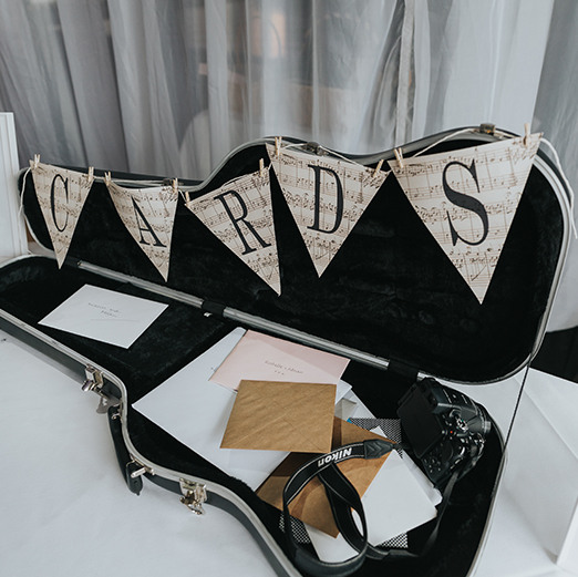 A guitar case sits open on a table with bunting attached for guests to leave their wedding cards