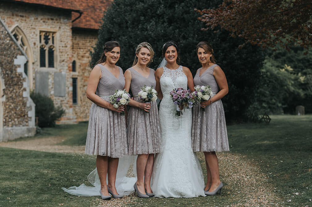 The bride and bridesmaids stand together with the maids wearing tea-length grey dresses with lace detail