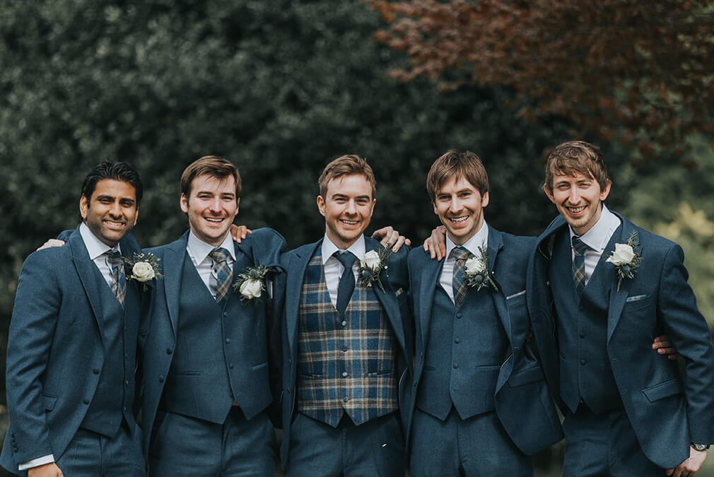 The groom and his groomsmen wore dark blue suits and the groom wore a tartan waistcoat to stand out