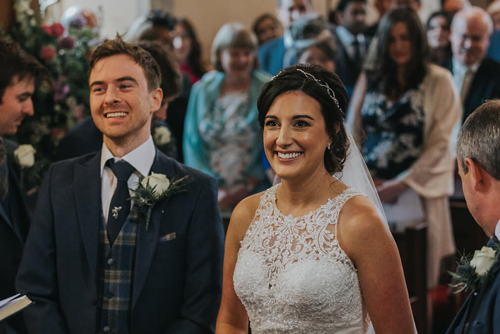 The bride and groom smile as they say their wedding vows during the wedding ceremony