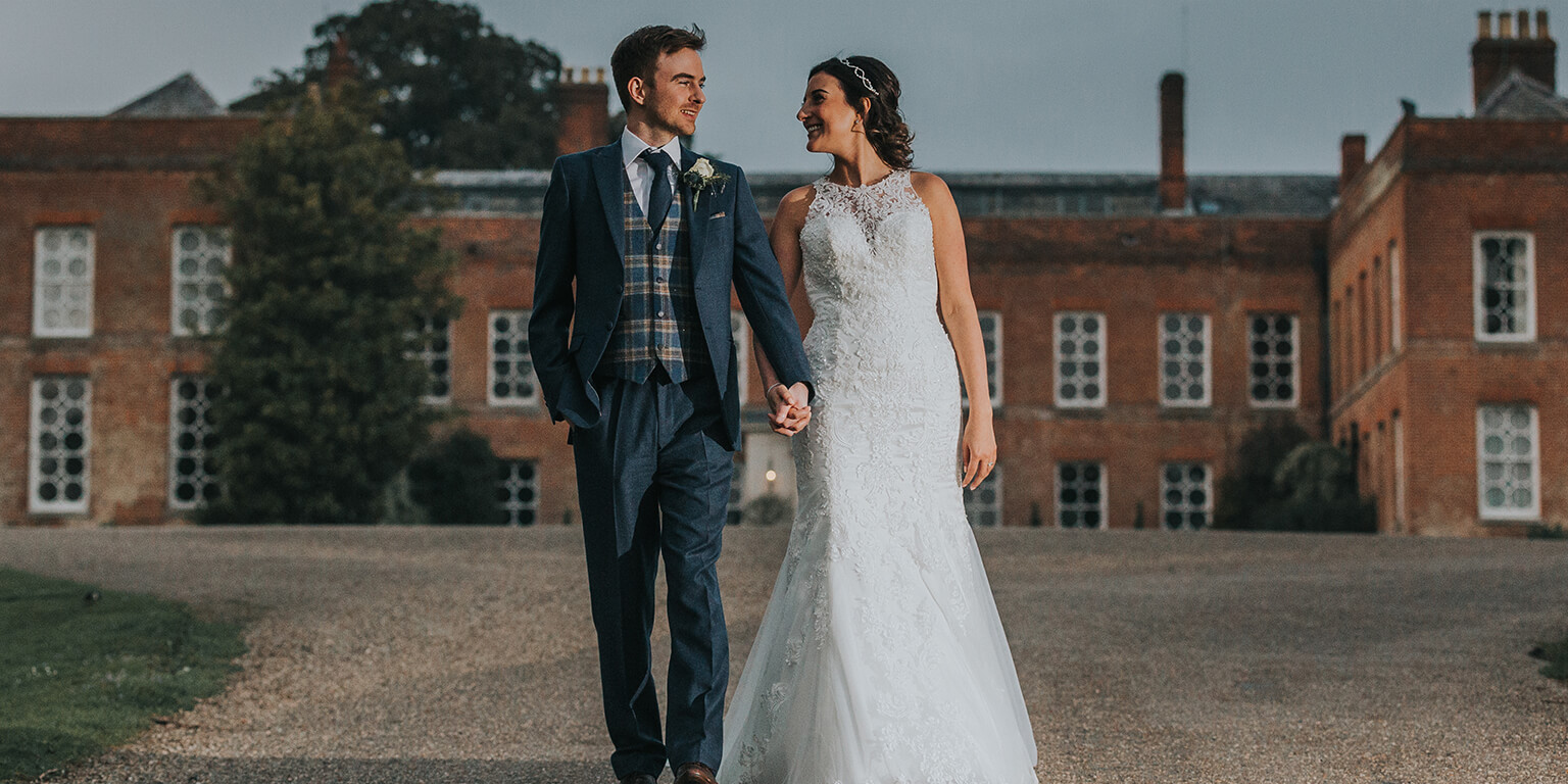 The happy couple walk hand-in-hand around the stunning estate at this beautiful Essex wedding venue
