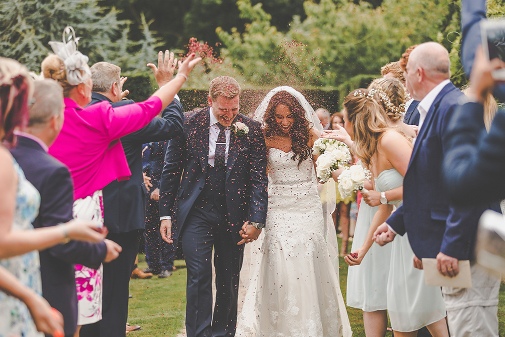 Guests congratulate a bride and groom with confetti as they leave their outdoor wedding ceremony