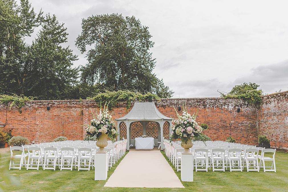 Chairs line either side of the wedding aisle in the walled garden ready for a beautiful outdoor wedding