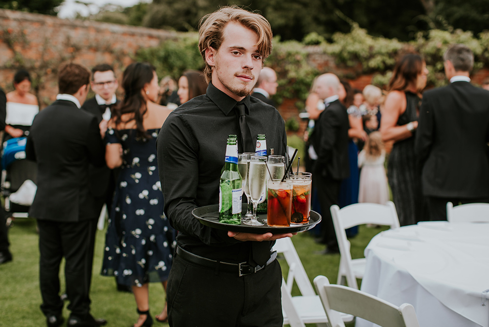 A waiter serves cold drinks to guests in the beautiful gardens at one of the finest wedding venues in Essex