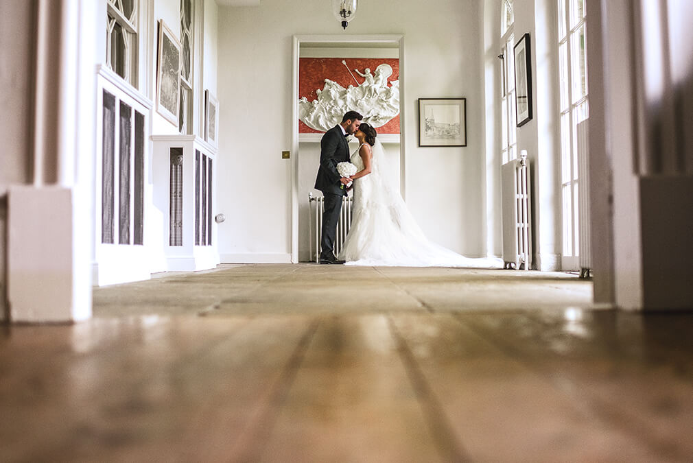 At this country house wedding venue in Essex the bride and groom steal a moment away from guests in the Georgian House