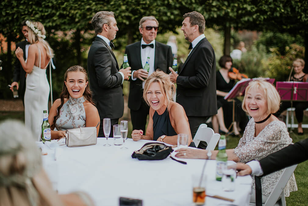 Wedding guests enjoy an outdoor wedding reception at Braxted Park wedding venue in Essex
