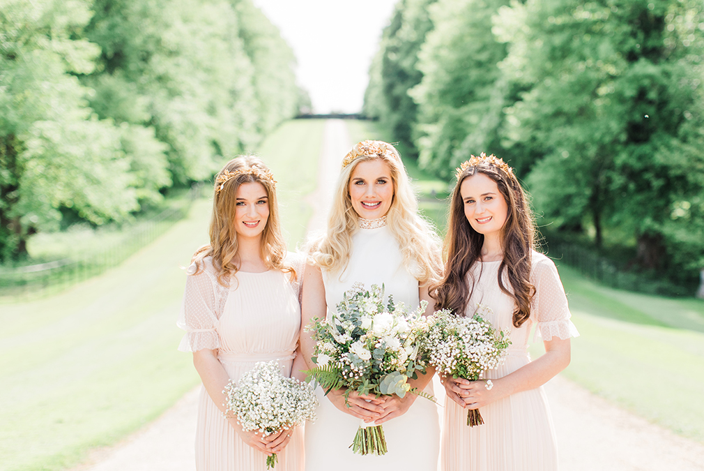 The bride and bridesmaids wear stunning gold tiaras as beautiful wedding accessories for a photoshoot at Braxted Park