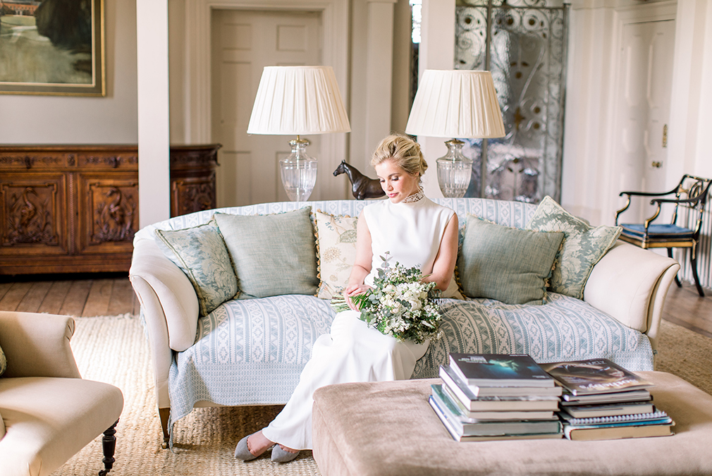 During a wedding photoshoot at Braxted Park in Essex the bride sits on an elegant sofa in a beautiful wedding dress
