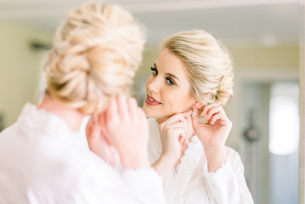 The bride puts in her earrings as she prepares for her wedding day at Braxted Park