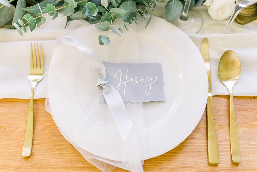 Grey table place name cards and gold cutlery make beautiful wedding place settings at Braxted Park