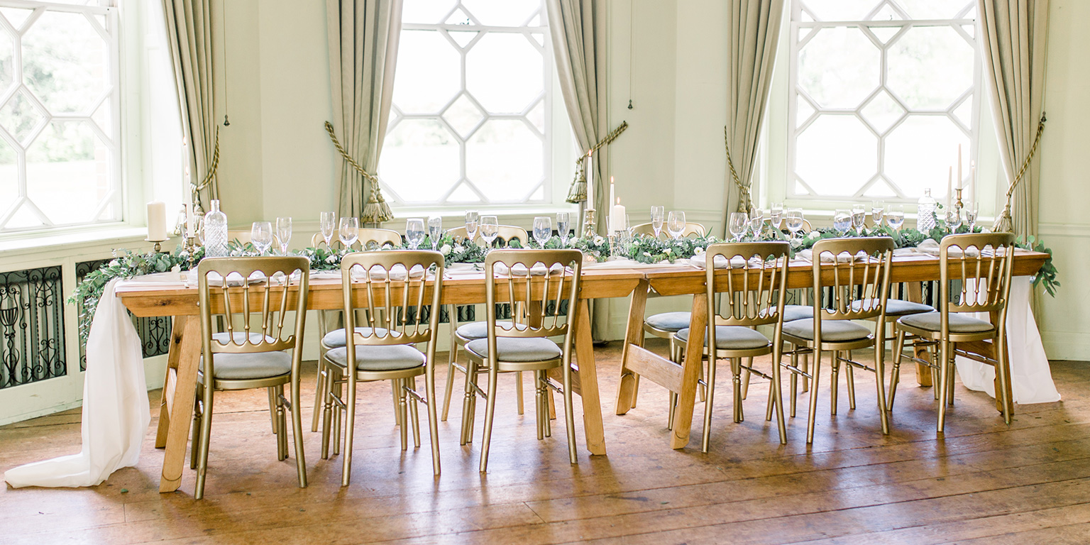 A trestle table is dressed in green, white and gold for a stunning styled photoshoot at Braxted Park