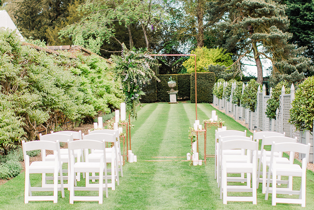 A white and gold inspired outdoor wedding ceremony set up in the gardens at Braxted Park wedding venue in Essex