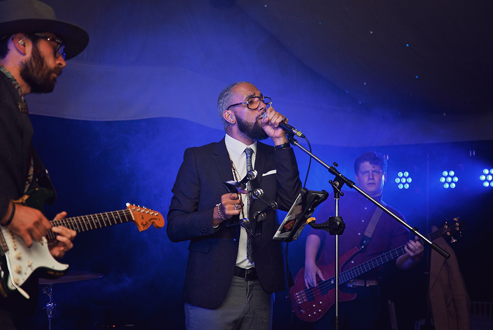 A wedding singer performs for guests at an evening wedding reception at Braxted Park