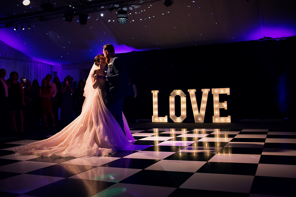 A couple perform their first dance in front of giant love letters during their wedding reception at Braxted Park
