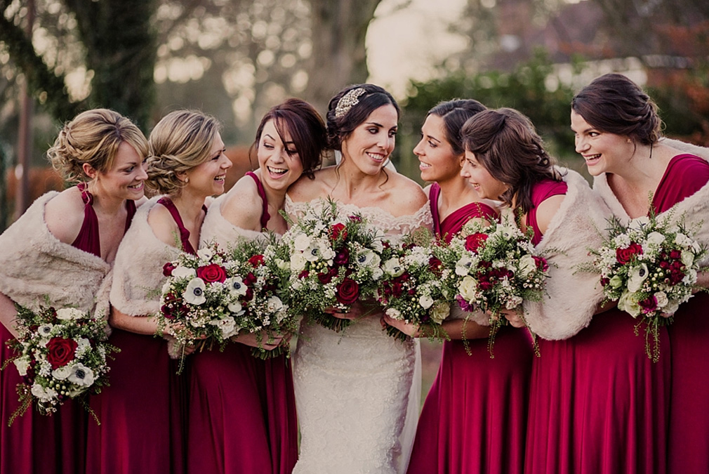 A bride enjoys time on her wedding day at Braxted Park with her bridesmaids who wear red bridesmaid dresses