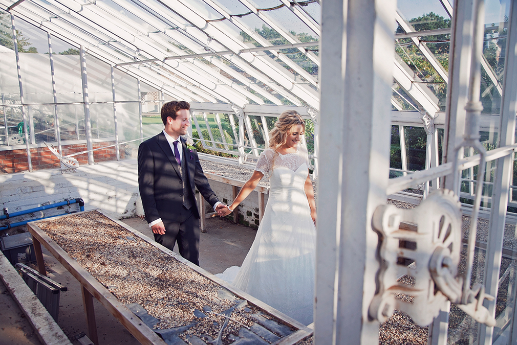 The bride and groom walk through one of the conservatories at Braxted Park on their wedding day