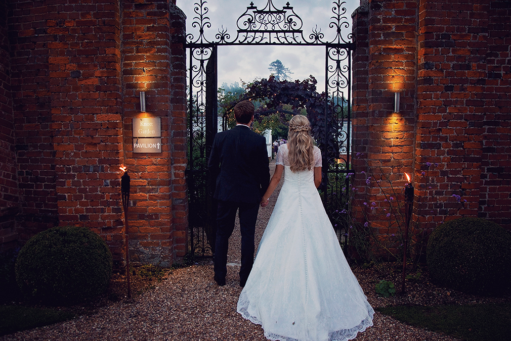The bride and groom walk through the grand gates in the gardens at Braxted Park wedding venue in Essex