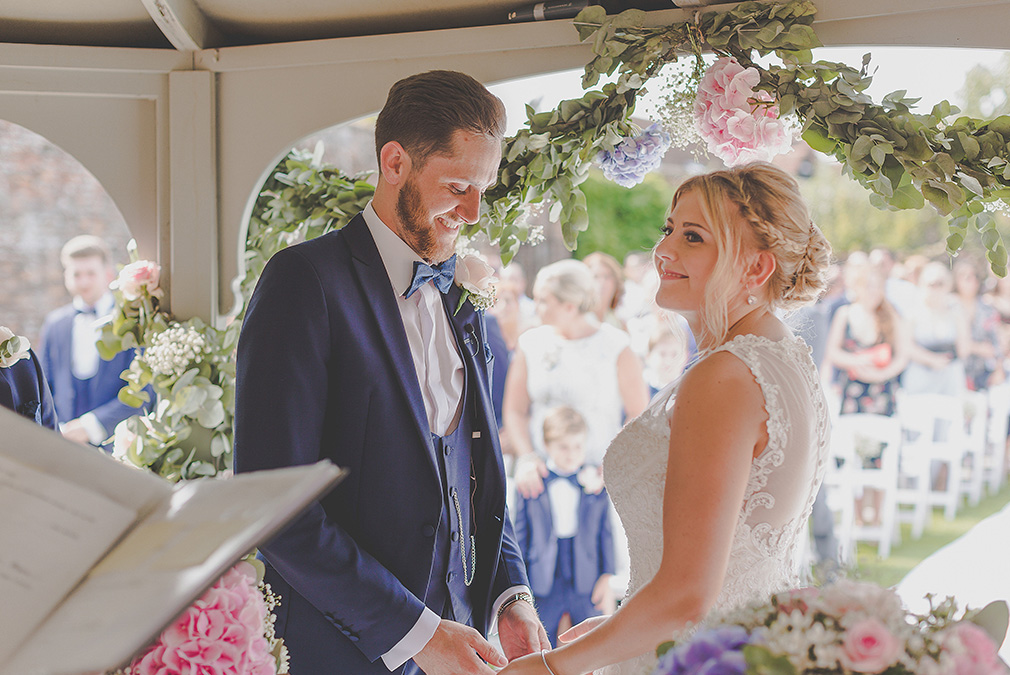 The bride and groom say their wedding vows at an outdoor ceremony at Braxted Park wedding venue in Essex