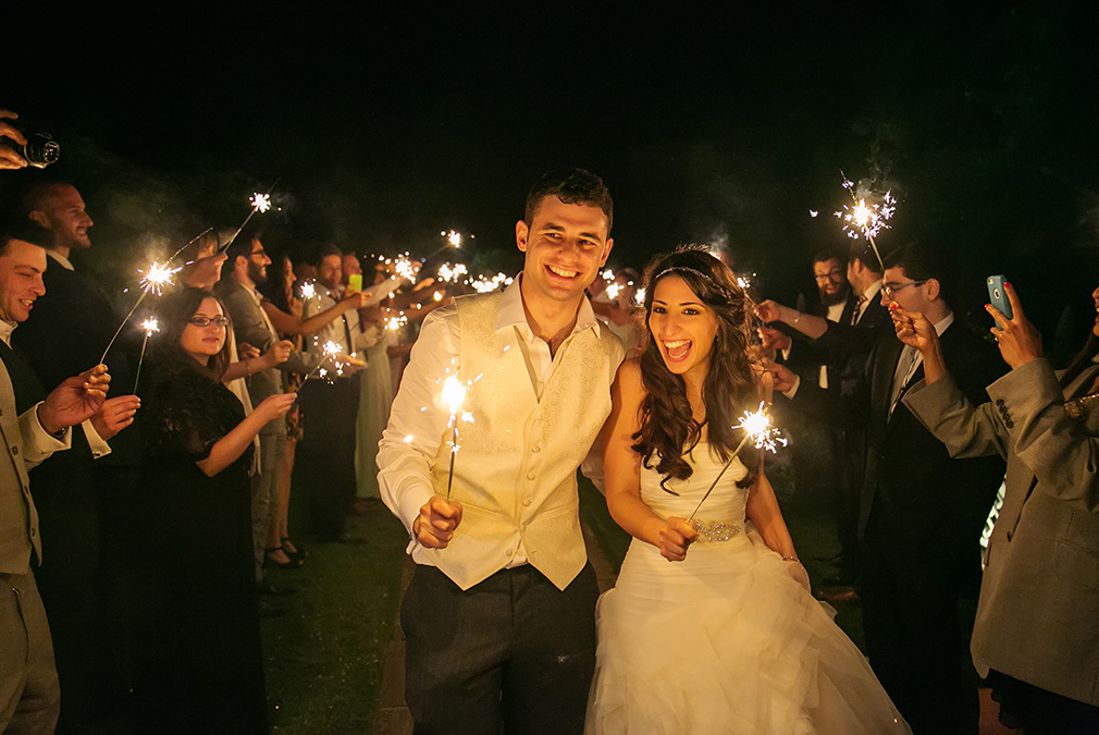Newlyweds enjoy sparklers during their evening wedding reception at Braxted Park wedding venue in Essex