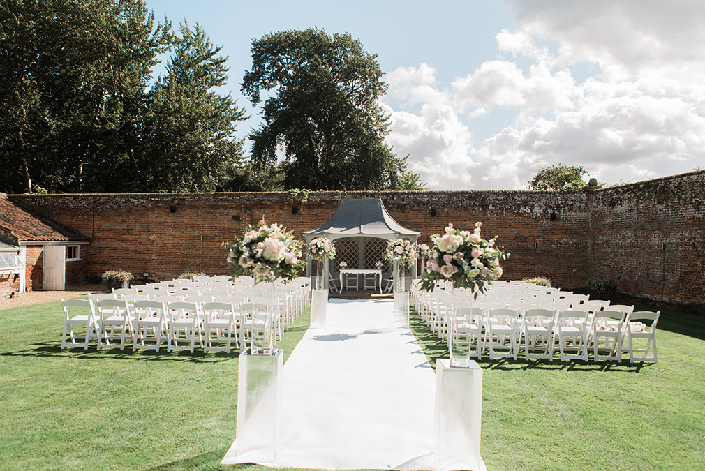 A beautiful outdoor ceremony set up in the walled garden at Braxted Park wedding venue in Essex