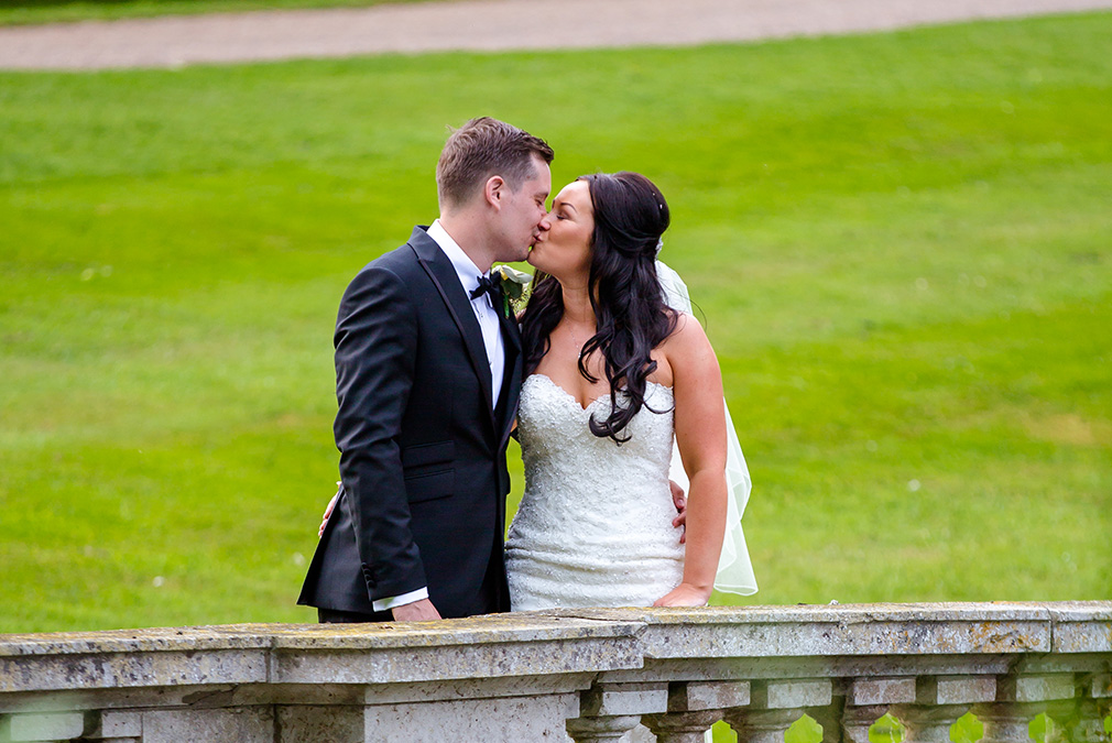 The bride and groom share a kiss as they explore the grounds at Braxted Park on their wedding day