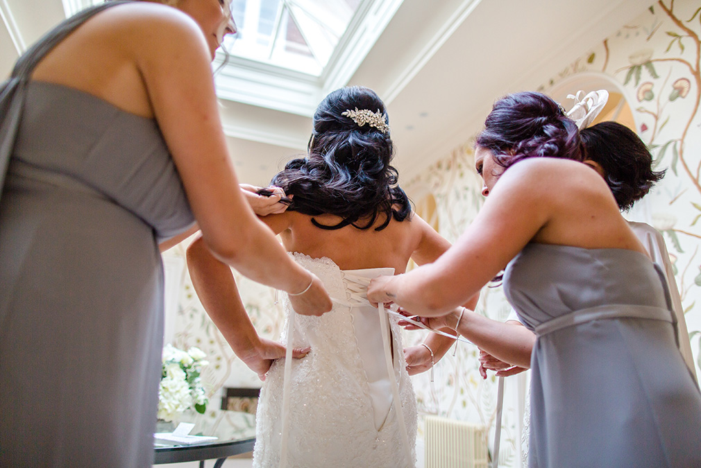 The bridesmaids help the bride into her wedding dress before her wedding ceremony at Braxted Park