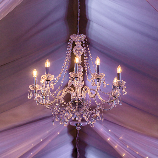 Chandeliers hung from the ceiling of the Pavillion at Braxted Park to add sparkle and elegance to this summer wedding