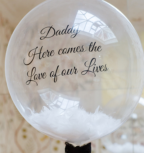 A giant balloon with 'Daddy here comes the love of our lives' was held by the couple's son as the bride walked down the aisle at Braxted Park