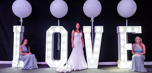 The bride stands with her bridesmaids in front of giant light up LOVE letters in the Pavillion at Braxted Park