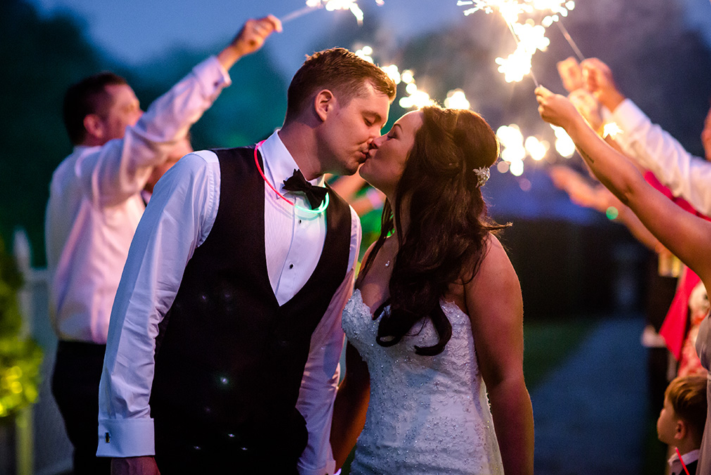 Newlyweds share a kiss during their sparkler exit at Braxted Park wedding venue in Essex