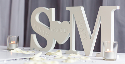 Personalised wooden letters are in the shape of the couple's initials and engraved with the date of their wedding at Braxted Park