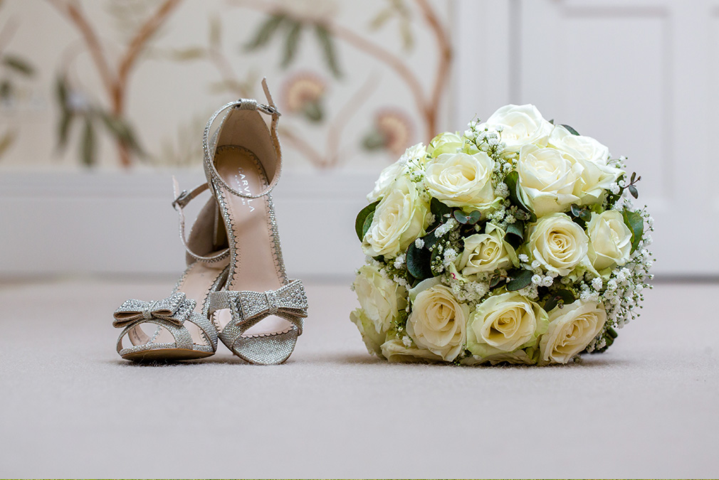 The bride wore gold wedding shoes and held a bouquet of white roses for her wedding day at Braxted Park
