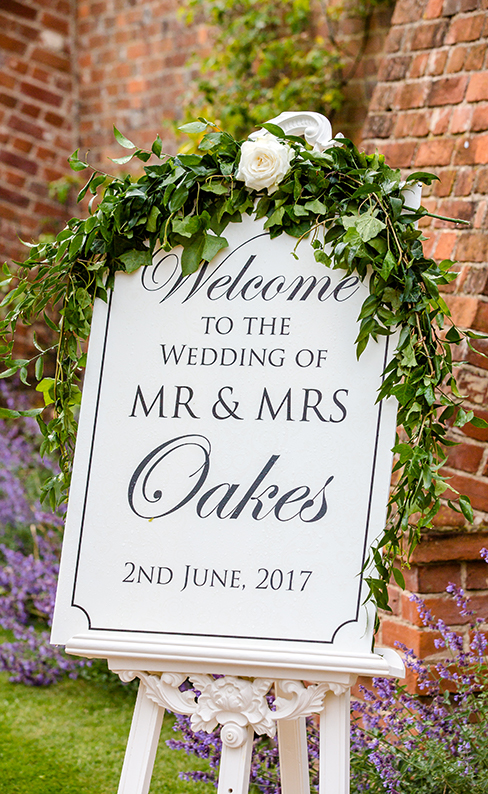 A black and white welcome wedding sign is adorned with wedding flowers and greets guests to the couples wedding at Braxted Park