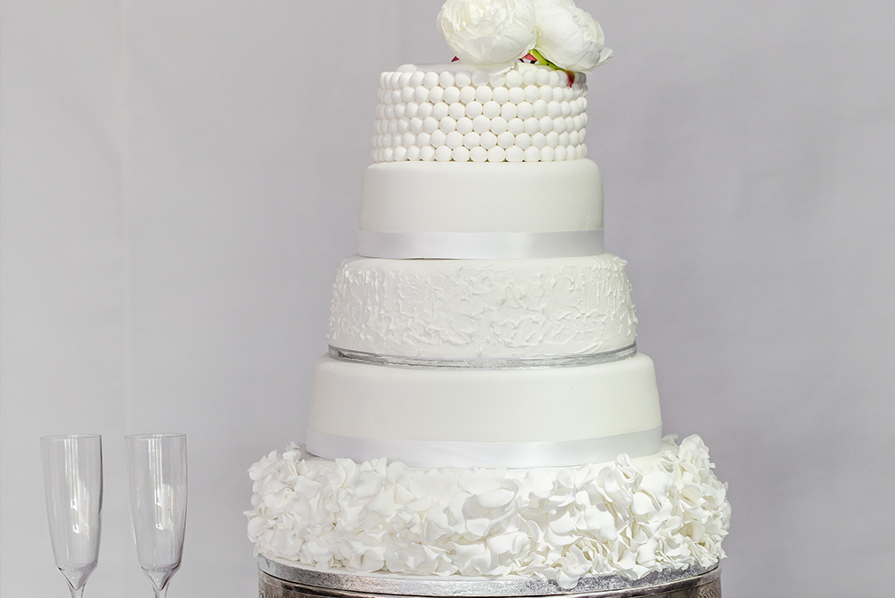 The couple chose an elegant five-tier all white wedding cake for their wedding at Braxted Park