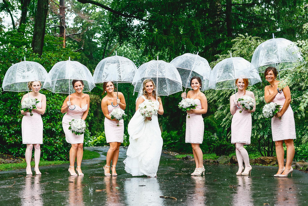 A bridal party use umbrellas to shelter from the rain on a spring wedding day