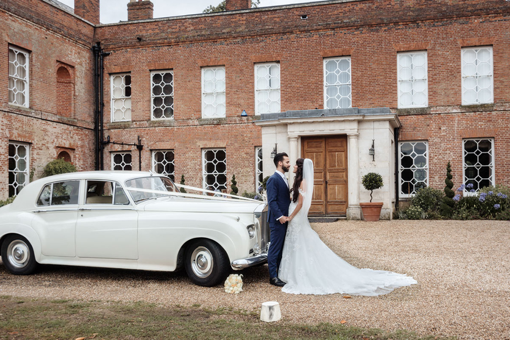 The bride and groom stand by their white wedding car in front of the house at Braxted Park wedding venue in Essex