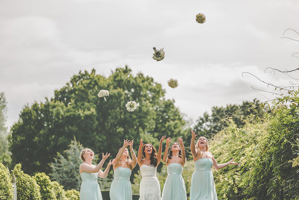 A bride and her bridesmaids celebrate after the wedding ceremony at Braxted Park by throwing their wedding bouquets in the air