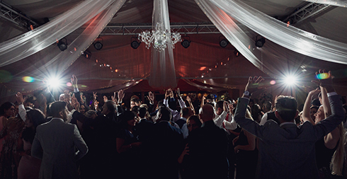 Guests hit the dance floor during an evening wedding reception at Braxted Park