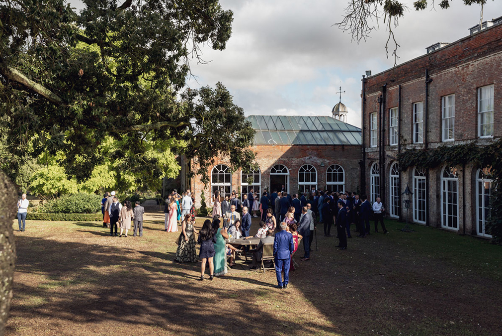 Guests enjoy an outdoor drinks reception outside the Orangery at Braxted Park