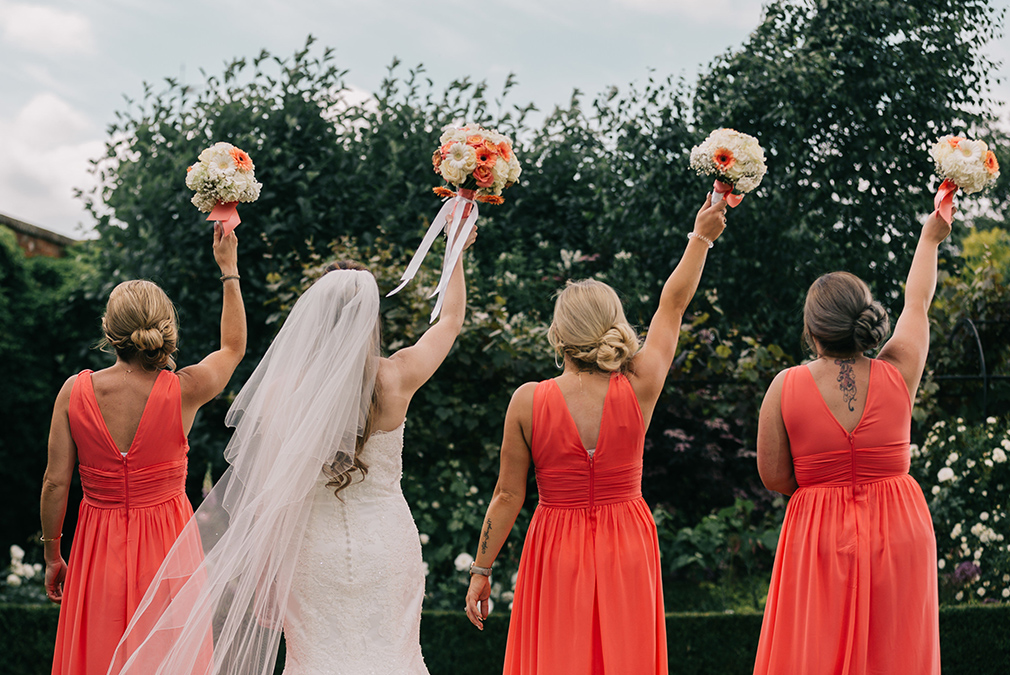 The bride stands with her bridesmaids who wore matching coral floor length dresses for this summer wedding at Braxted Park