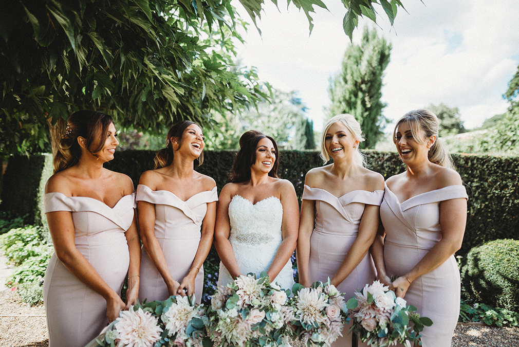 The bride and her bridesmaids make the most of the gardens during an outdoor wedding at Braxted Park