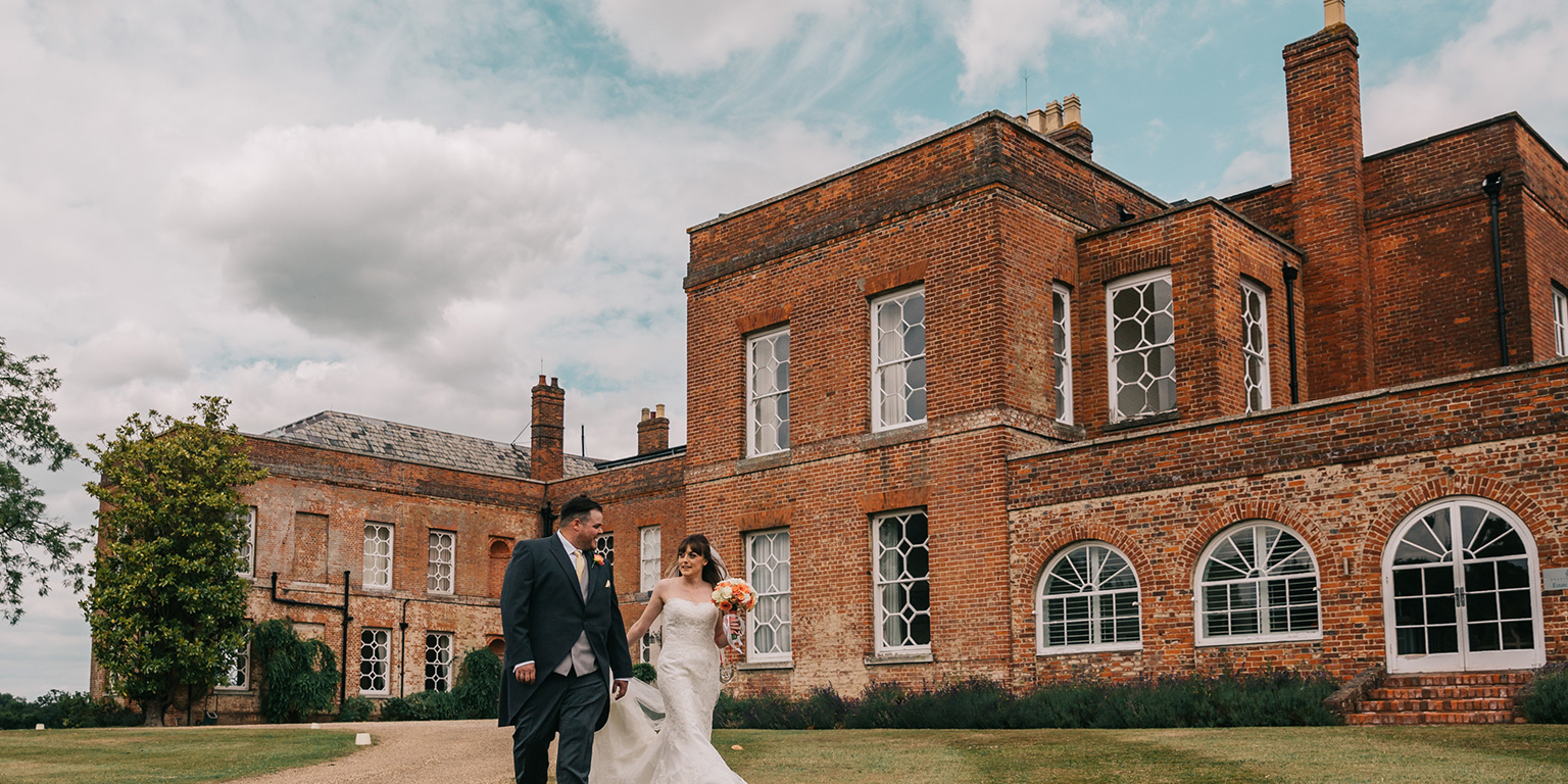 The bride and groom take a walk around the grounds at Braxted Park on their wedding day